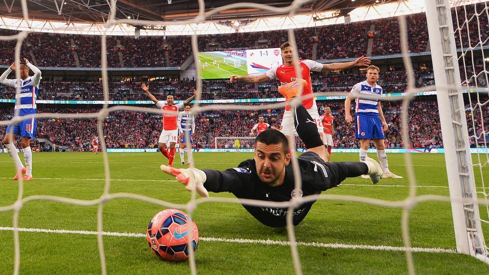 Kiper Reading memungut bola dari gawangnya saat Arsenal sukses membuat gol