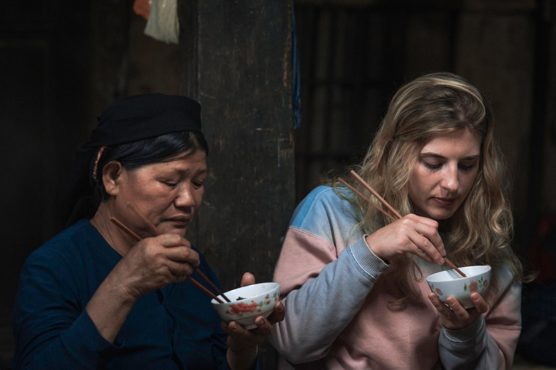 ilustrasi dua orang berbeda bangsa makan dengan sumpit | photo by digital sennin from unsplash
